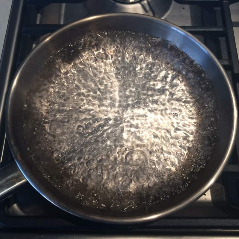 Boiling water in a stainless steel pan apparently fills the pores with water, stopping your food from sticking
